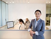 Businesswoman standing near office cubicles