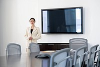 Businesswoman standing in empty conference room