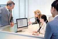 Businesswoman reviewing co_worker's work on monitor