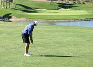 Golfer with iron club looking at putting green in distance about to hit ball over water hazard