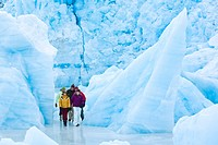 Group walking amongst icebergs frozen in Portage Lake at Portage Glacier, Chugach National Forest, Southcentral Alaska