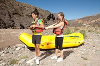Couple putting on lifejackets for white water rafting (thumbnail)