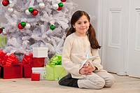 Young girl kneeling by Christmas tree