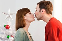 Mid adult couple kissing at Christmas time
