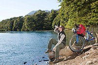 Mountain biker drinking by lake