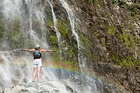 Woman standing by waterfall with arms open