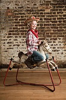 Young girl dressed as cowgirl with rocking horse