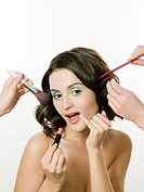 Young woman having hair and makeup done