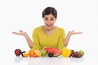 Woman with assorted fresh fruits and gesturing