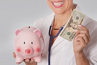 Female doctor holding a currency note and a piggy bank
