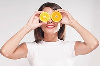 Woman holding orange halves over her eyes