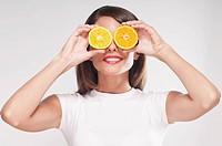 Woman holding orange halves over her eyes