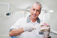 Dentist using a toothbrush on dentures