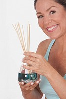 Woman holding an aromatherapy oil bottle with incenses
