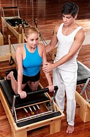 Male instructor assisting a woman in a gym
