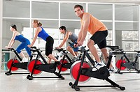 Men and women working out on exercise bikes in a gym