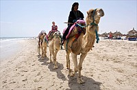 Tunesia, Djerba, Midoun, children enjoying a camel ride on the beach