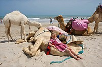 Tunesia, Djerba, Midoun, girl posing for photo together with a camel