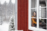 Young woman sitting in window, with snow outside