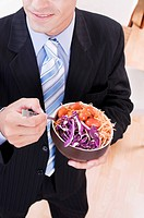 Businessman eating salad in a restaurant