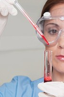 Female lab technician analyzing a blood sample in a test tube