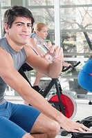 Man drinking water with two women working out in a gym