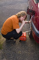 A man syphoning petrol from a cars petrol tank in the uk
