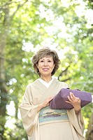 Mature woman in Kimono holding gift, smiling, Kyoto city, Kyoto prefecture, Japan