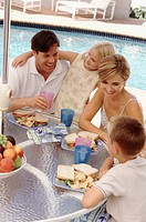 Family eating lunch by the pool