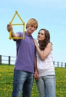 Young couple holding folding ruler shaped as house, planning new home in nature