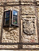 Detail of window and coat of arms on a wall, Oña, Burgos province, Castilla-Leon, Spain