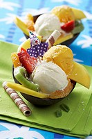 Tropical ice cream sundaes with orange ice cream, coconut ice cream & fruit