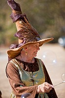 Gainesville FL - January 2009 - Senior woman dressed in period clothing as a witch entertains children with bubbles at Hoggetowne Medieval Faire in Ga...