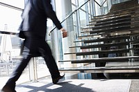 Rushing businessman walking towards office staircase