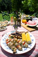 Corn on cob and skewers on table in backyard