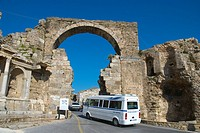 Dolmus minibus going through ancient gate Side Mediterranian coast Anatolia region Turkey Asia
