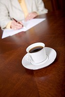 cup of espresso on the table while a business woman is signing some papers