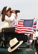 England, West Sussex, Goodwood Revival. Girl with binoculars watching car races at Goodwood Revival.