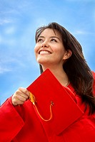 Female graduate throwing the mortarboard outdoors