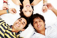 girl and two men smiling on the floor looking happy isolated over a white background