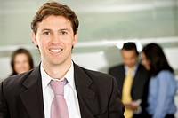 Businessman smiling in an office with his team behind him
