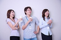 Three colleagues holding drink together and looking away with smile