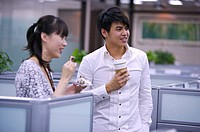 Young woman and man eating or drinking at coffee break and smiling