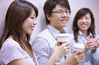Three colleagues holding coffee and smiling together (thumbnail)