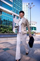Young woman walking and holding briefcase with smile