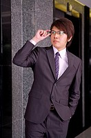 Young businessman looking away and holding glasses