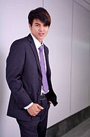 Young businessman standing and looking at the camera with smile