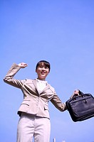 Young woman standing with fist up and holding briefcase with smile