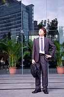 Young businessman holding briefcase and looking up