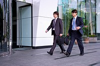 Two businessmen holding briefcase and walking